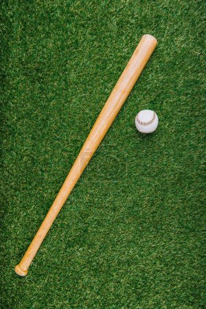 top view of baseball bat and ball arranged on green lawn