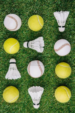 top view of arrangement of badminton shuttlecocks, tennis and baseball balls on green lawn