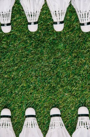 Photo for Top view of white shuttlecocks arranged on green grass - Royalty Free Image