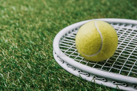 close up view of tennis ball on racket lying on green lawn