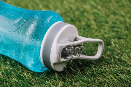 Photo for Close up view of sportive water bottle lynig on green grass - Royalty Free Image