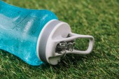 close up view of sportive water bottle lynig on green grass