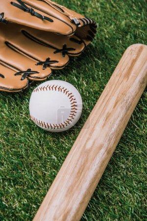 close up view of baseball equipment arranged on green grass