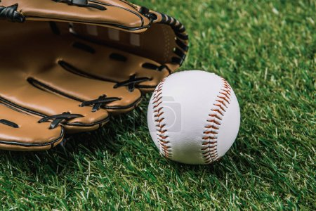 close up view of baseball ball and glove lying on green grass