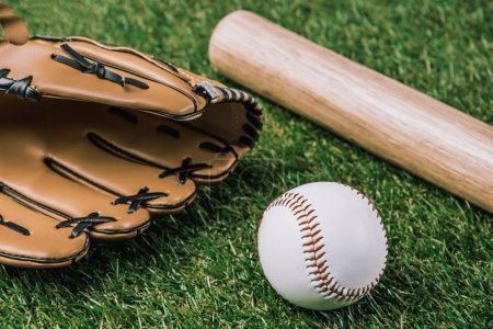 Photo pour Bouchent la vue de l'équipement de baseball disposé sur l'herbe verte - image libre de droit