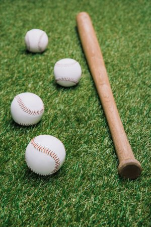 close up view of baseball bat and balls arranged on green lawn