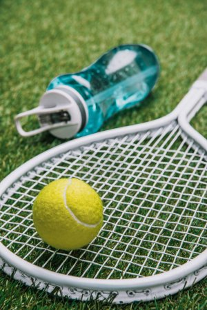 close up view of tennis equipment and sportive water bottle on green grass
