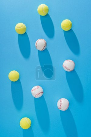 top view of arranged tennis and baseball balls on blue backdrop