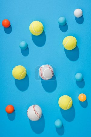 top view of arranged pin pong, tennis and baseball balls on blue background