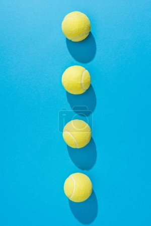 top view of arranged tennis balls on blue background