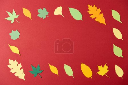 frame made of colorful papercrafted leaves arrangement on red background