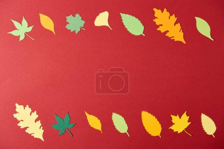 flat lay with colorful papercrafted leaves arrangement on red background