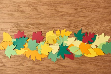 top view of colorful papercrafted foliage arrangement on wooden background
