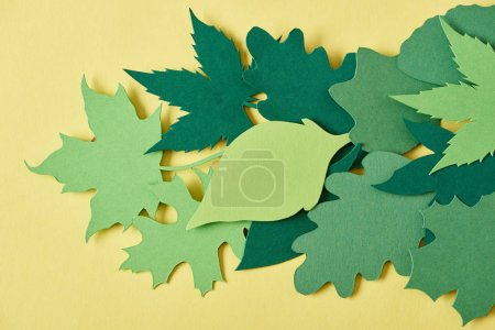 full frame of green handcrafted paper foliage arranged on yellow backdrop