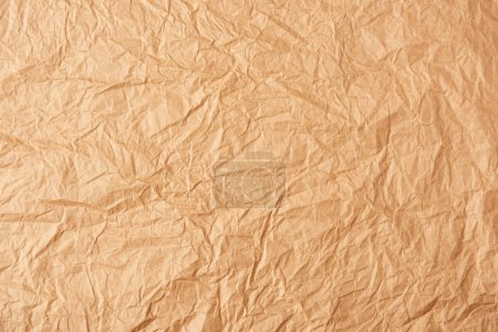 full frame of beige crumpled paper as background