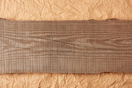 top view of wooden plank on crumpled paper backdrop