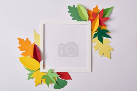 Photo for Flat lay with handcrafted paper leaves and empty frame on white tabletop - Royalty Free Image