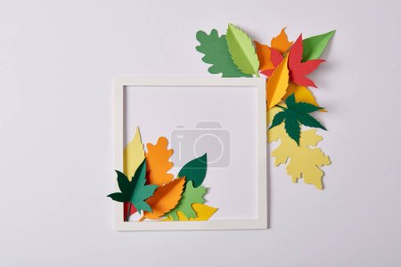 flat lay with handcrafted paper leaves and white frame on white tabletop
