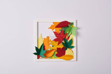 Photo for Flat lay with handcrafted paper leaves and frame on white tabletop - Royalty Free Image