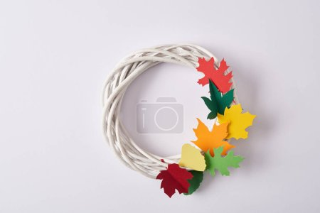 top view of handmade wreath with colorful paper foliage on white backdrop