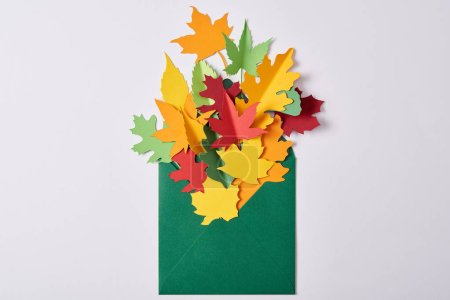 top view of colorful handcrafted paper leaves in green envelope on white background