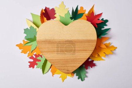 top view of wooden heart shaped board and colorful handcrafted leaves on white surface