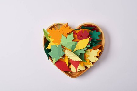 Photo for Top view of wooden heart shaped box and colorful handcrafted leaves on white surface - Royalty Free Image