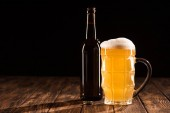 bottle of beer and mug of fresh light beer with foam at wooden table, minimalistic concept