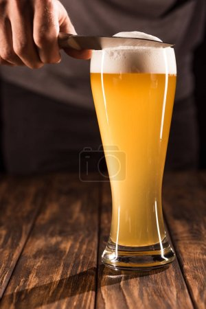 partial view of man taking off beer foam from mug by knife at wooden table