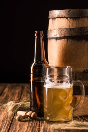 glass of light beer with foam, beer bottle, wheat and wooden barrel at table on black background