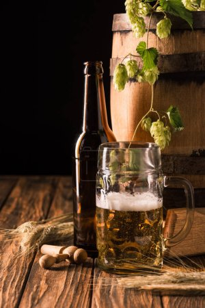 beer bottle, glass of fresh beer with foam, hop, wheat and wooden barrel at table on black background