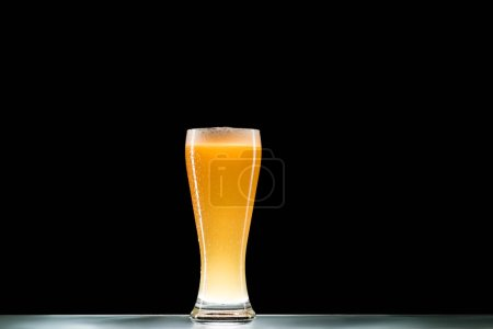 кружка светлого холодного пива с пеной за столом на черном фоне, минималистичная концепция