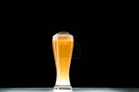 стакан свежего пива с пеной за столом на черном фоне, минималистичная концепция