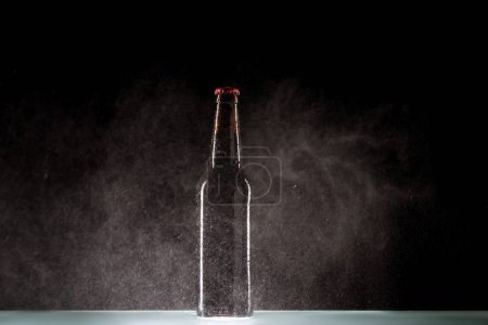 beer bottle with spraying water around at surface on black background