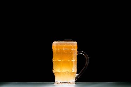 кружка светлого свежего пива за столом на черном фоне, минималистичная концепция