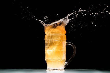 mug of light  beer with foam and splashes at table on black background, minimalistic concept