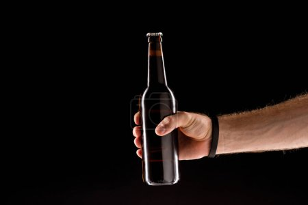 cropped image of man holding beer bottle isolated on black background