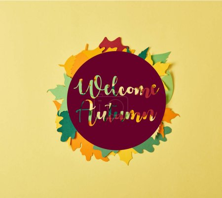 """flat lay with colorful papercrafted foliage with """"welcome autumn"""" lettering in circle on yellow background"""