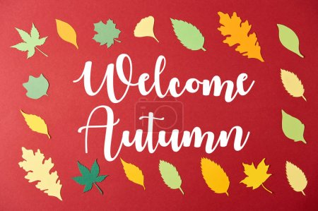 "frame made of colorful papercrafted leaves with ""welcome autumn"" inspiration on red background"
