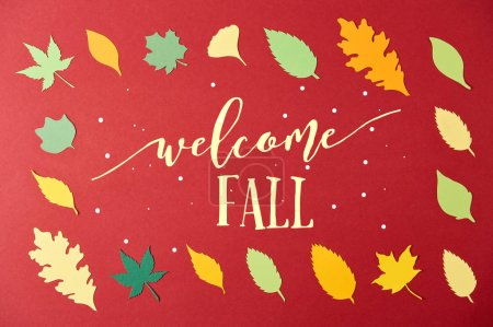 "frame made of colorful papercrafted leaves with ""welcome fall"" lettering on red background"