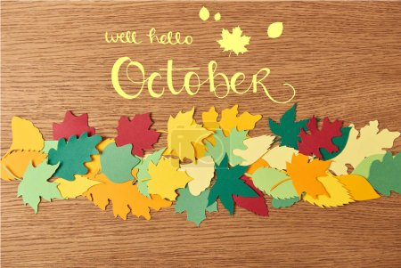 "top view of colorful papercrafted foliage with ""well hello october"" lettering on wooden background"