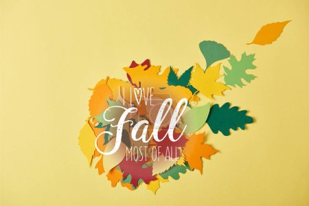 "flat lay with colorful papercrafted foliage with ""I love fall most of all"" inspiration on yellow background"