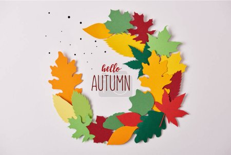 """flat lay with colorful papercrafted foliage with """"hello autumn"""" lettering on white background"""