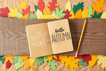 """flat lay with """"hello autumn"""" lettering in notebook, pencil on wooden plank and colorful handcrafted paper leaves on crumpled paper background"""