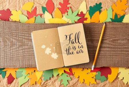 "flat lay with ""fall is in the air"" inspiration in notebook, pencil on wooden plank and colorful handcrafted paper leaves on crumpled paper background"