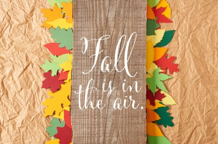 "top view of wooden plank with ""fall is in the air"" inspiration and colorful paper leaves arrangement on crumpled paper backdrop"