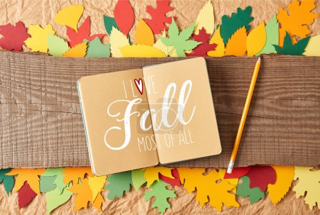 "flat lay with ""I love fall most of all"" inspiration in notebook, pencil on wooden plank and colorful handcrafted paper leaves on crumpled paper background"