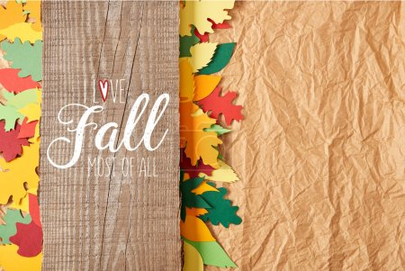 "top view of wooden plank with ""I love fall most of all"" inspiration and colorful paper leaves arrangement on crumpled paper backdrop"
