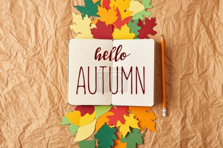 "flat lay with ""hello autumn"" inspiration in notebook, pencil and colorful handcrafted paper leaves on crumpled paper background"