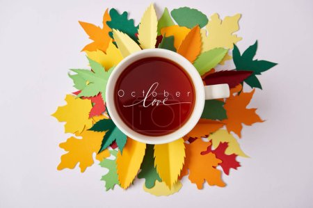"top view of cup of tea with ""october love"" inspiration on colorful handcrafted leaves on white surface"